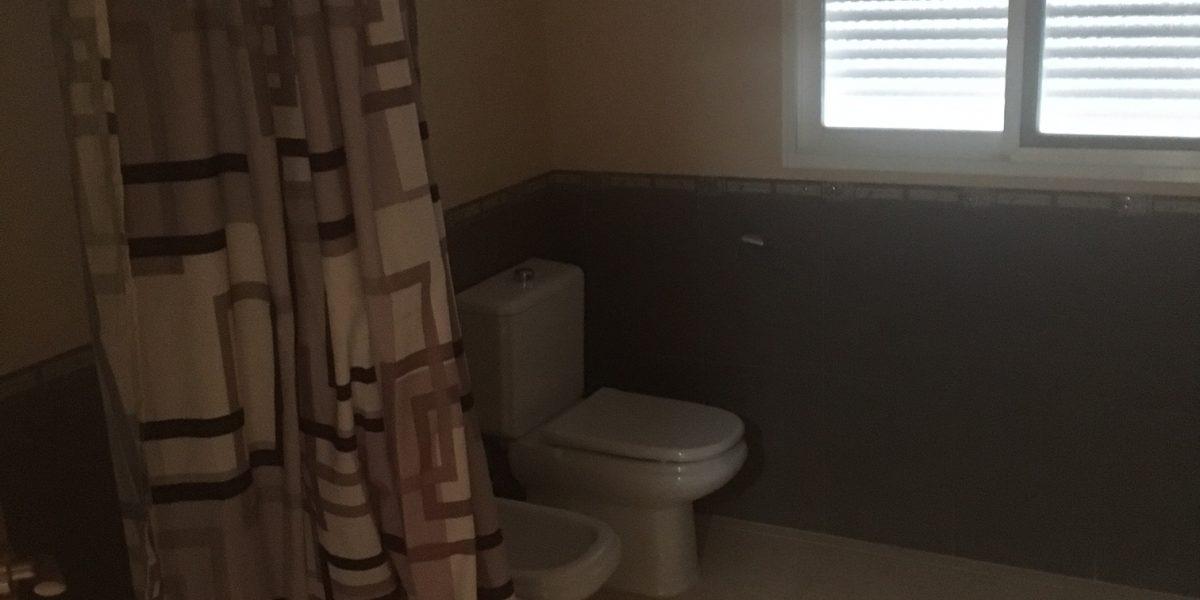 Baño con videt, bañera y armario empotrado.